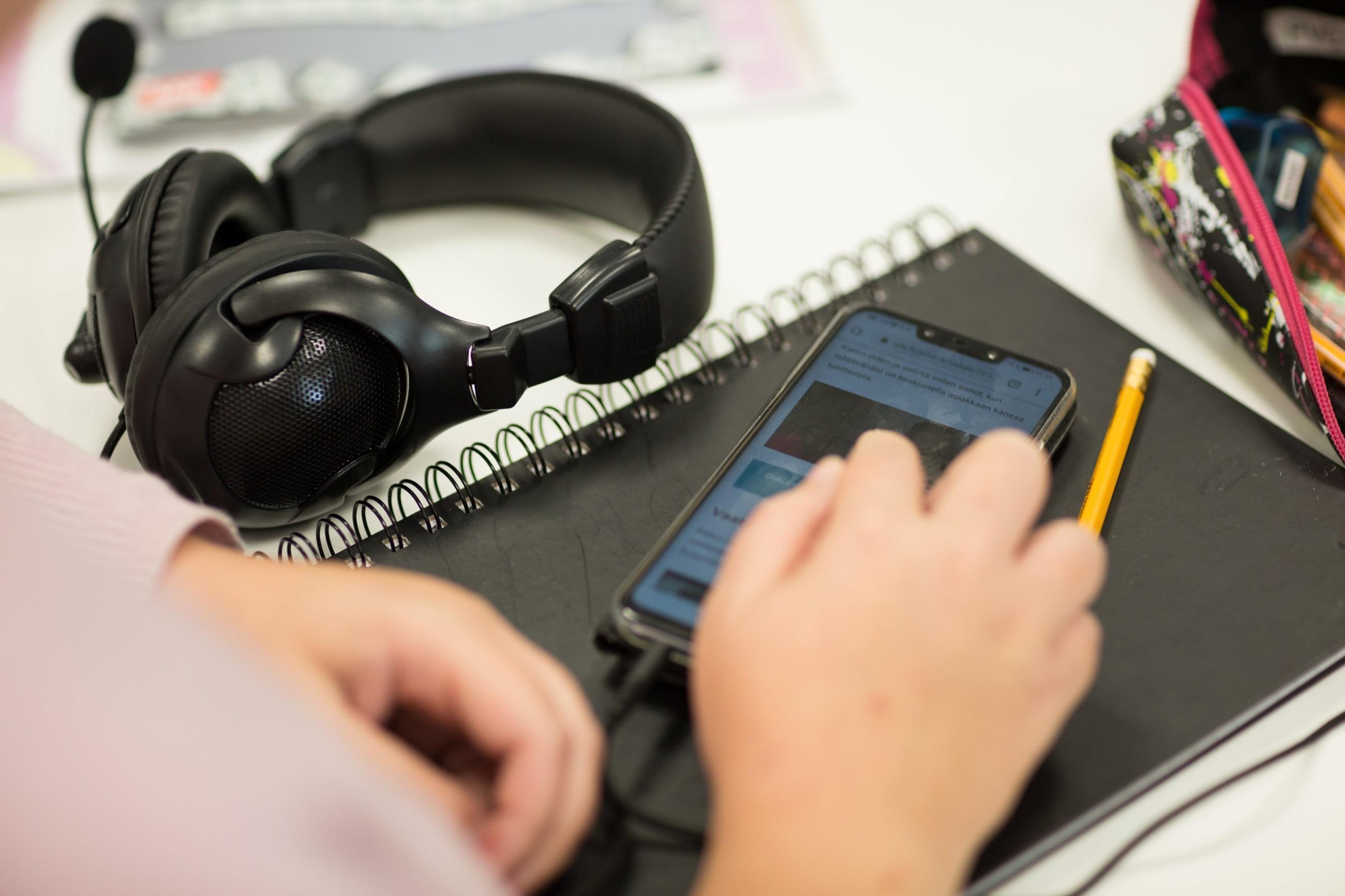 Pöydällä headset-kuulokkeet, kännykkä ja muistiinpanovälineet, kuvassa näkyvät myös henkilön kädet.