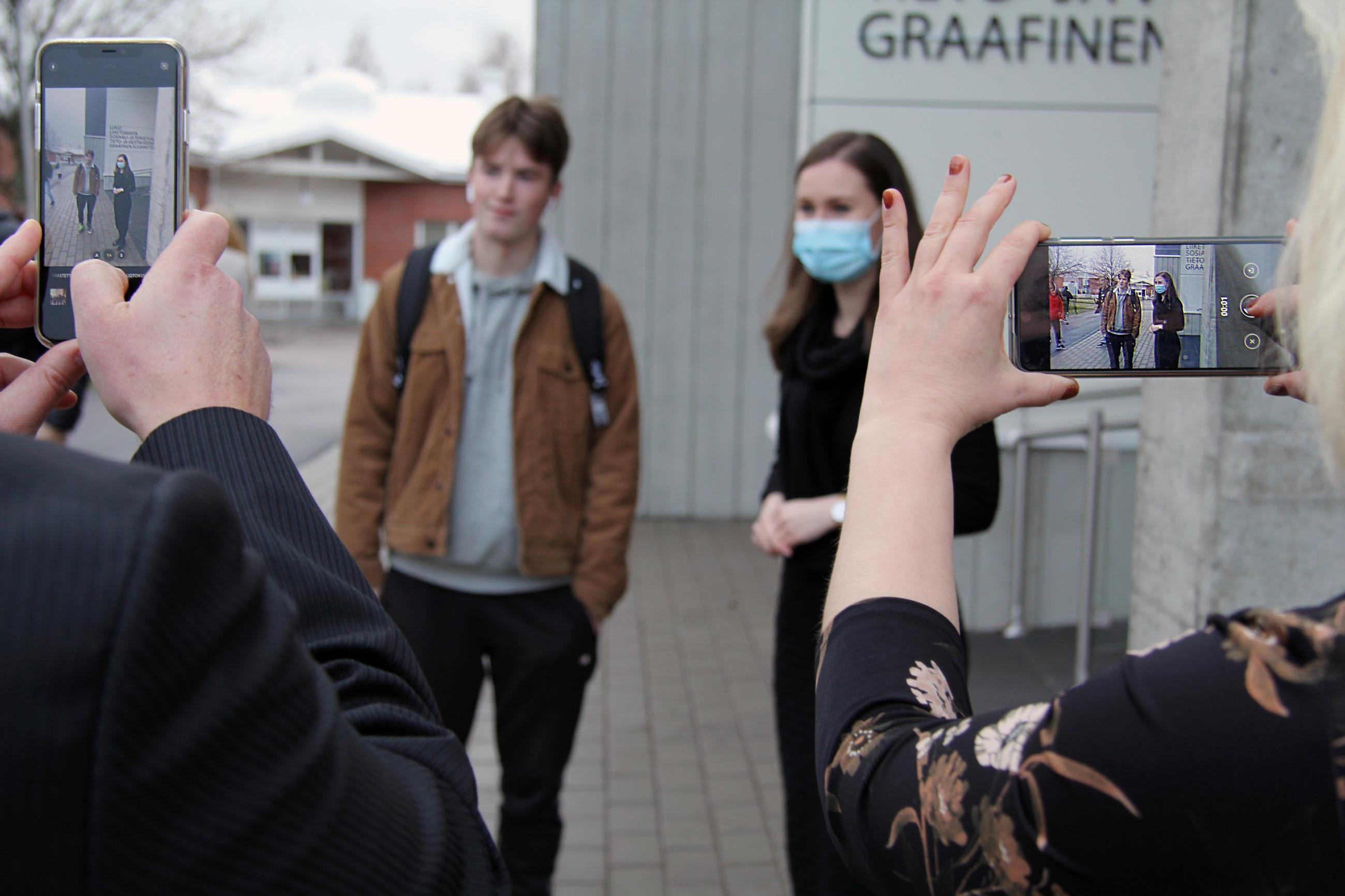 Opiskelija ja pääministeri Sanna Marin, etualalla ihmiset ottavat kuvia kännyköillä.
