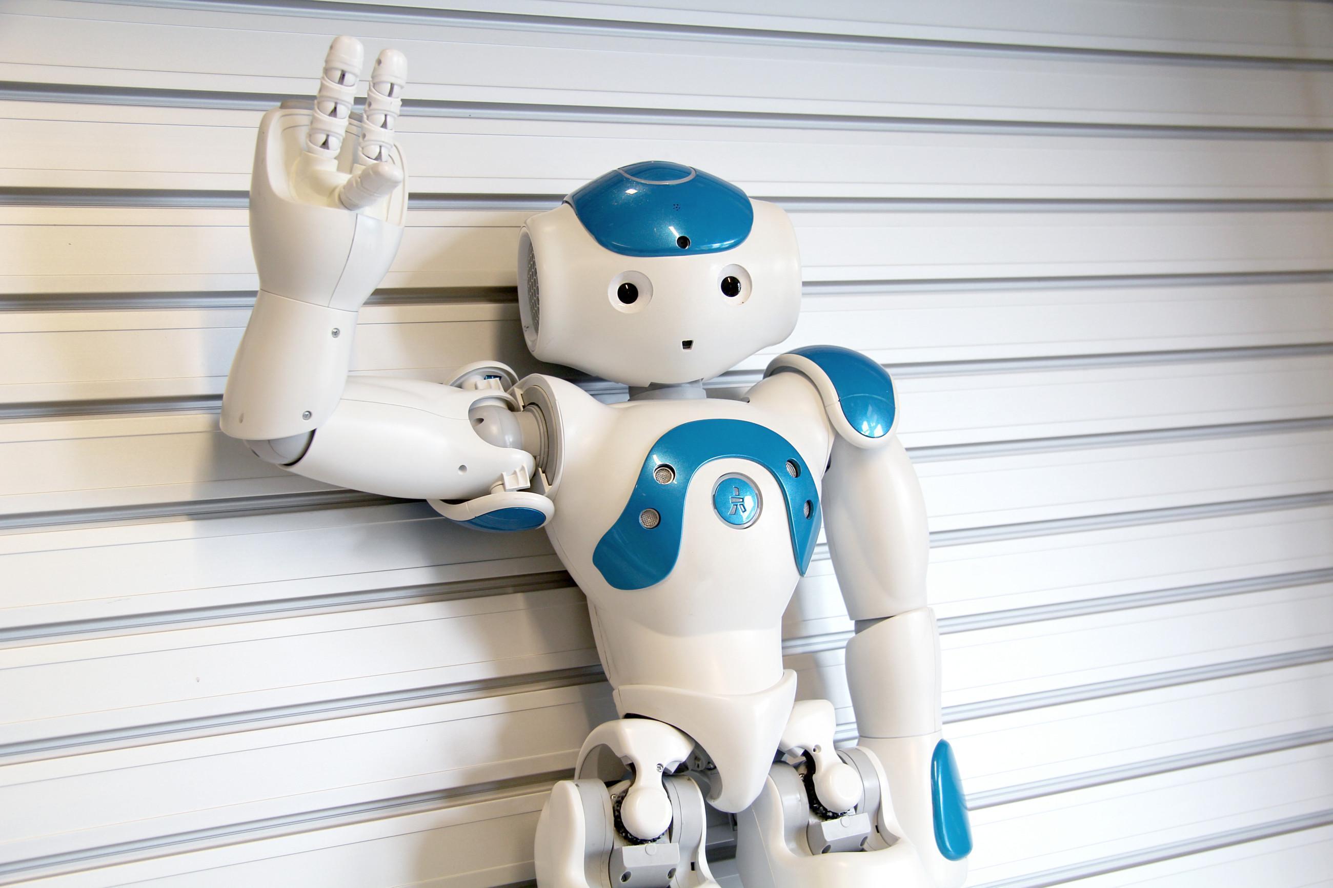 Sinivalkoinen Nao-robotti käsi tervehdysasennossa.