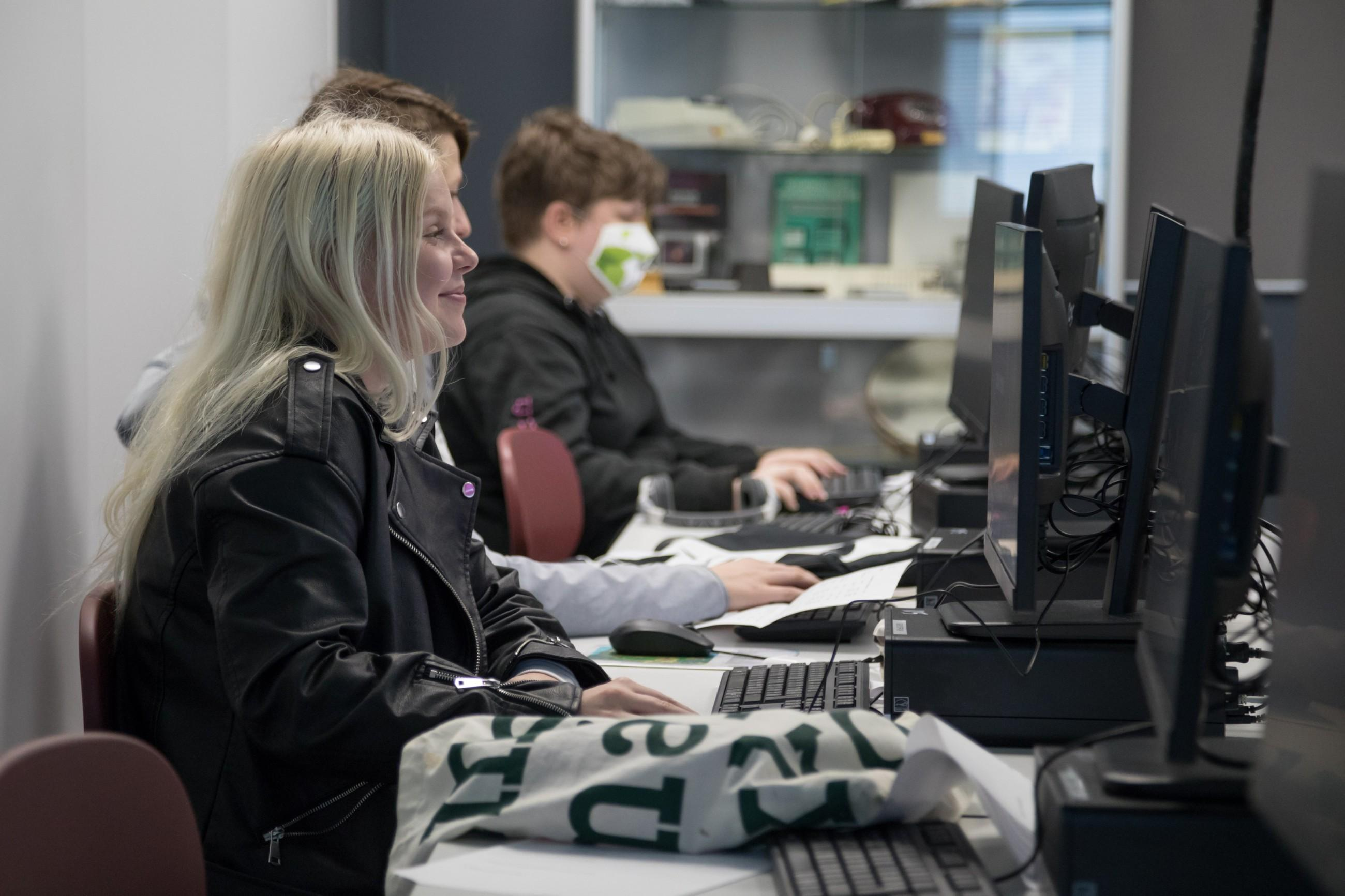 Opiskelijoita tietokoneen äärellä.