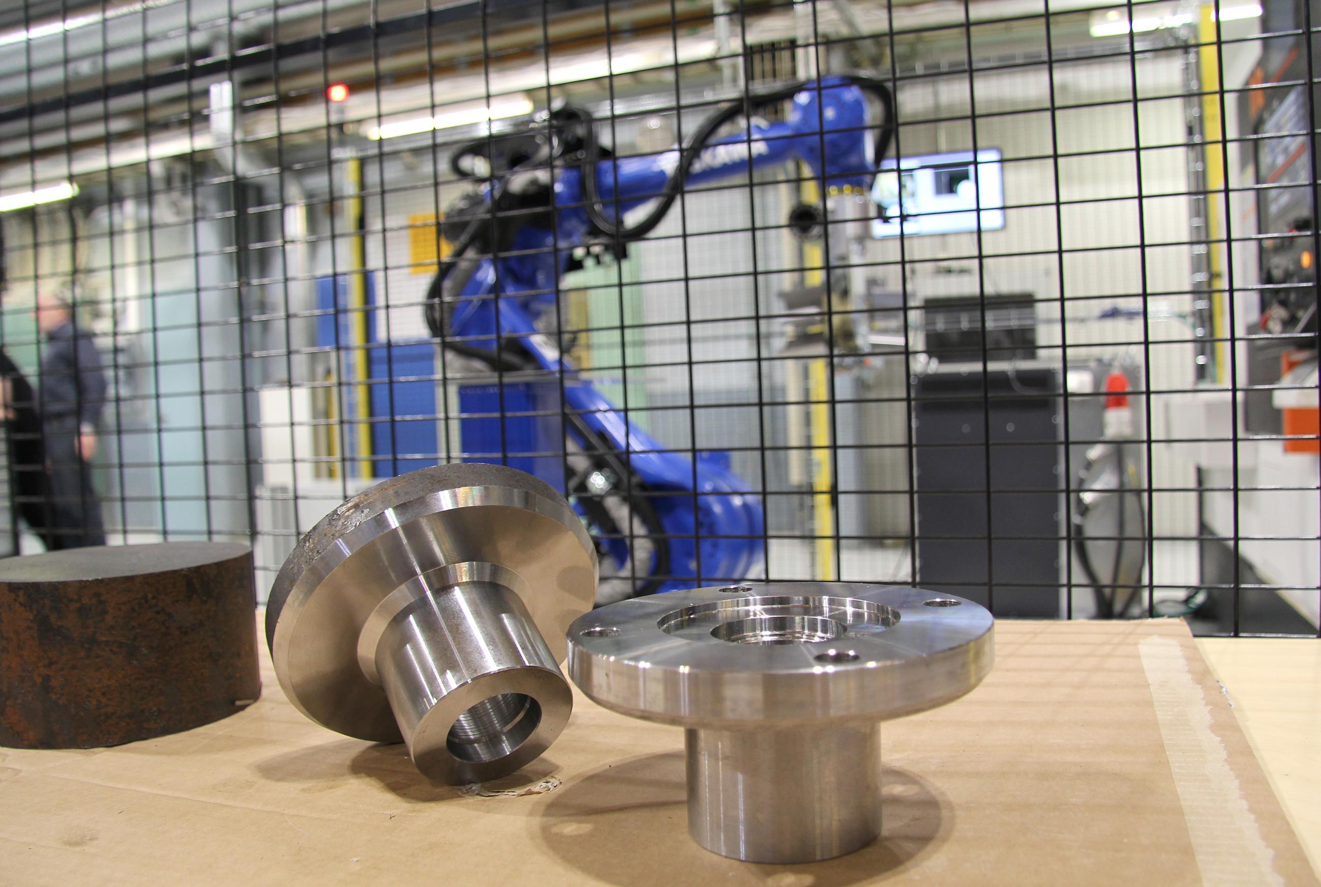 Kuvassa etualalla metalliosia, taustalla verkkoaidan takana sininen teollisuusrobotti.