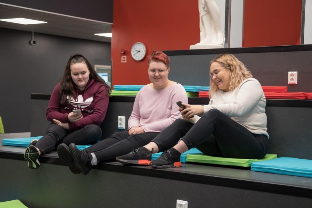 Kolme iloista opiskelijatyttöä istuvat pehmustetuilla rappusilla ja tutkivat kännyköitä.