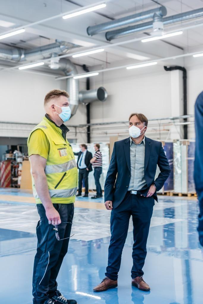 Kaksi miestä seisoo teollisuushallissa, toisella päällään keltainen huomioliivi, kummallakin kasvomaski.