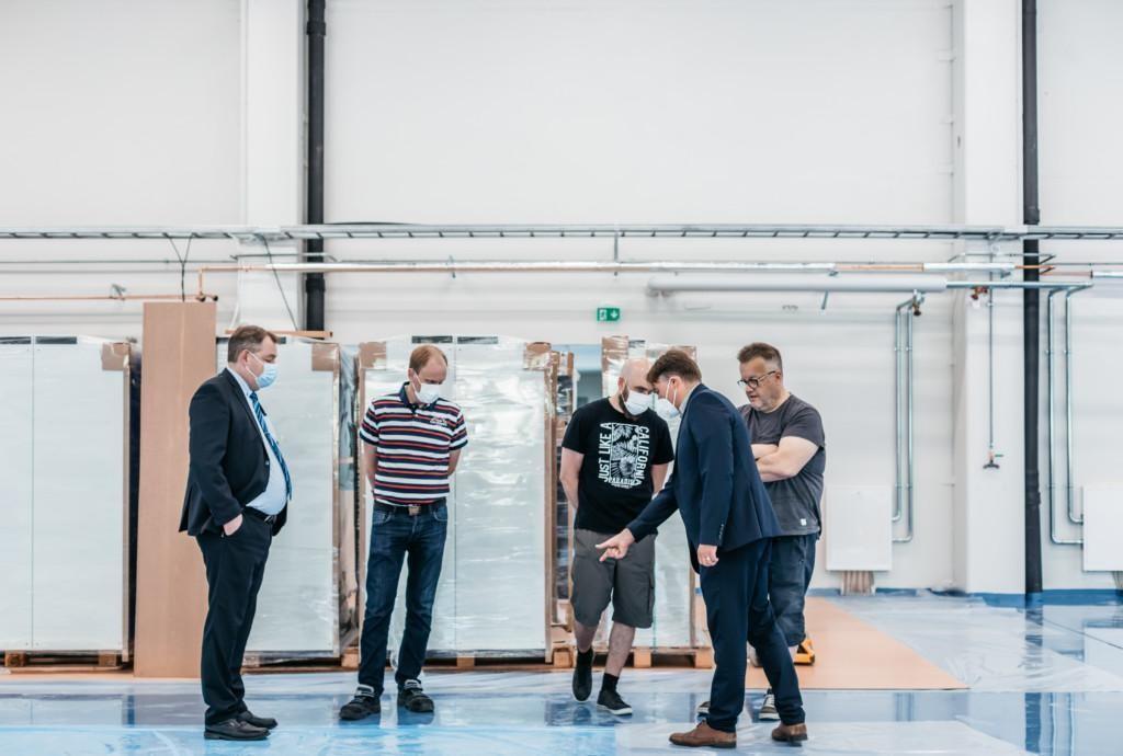 Viisi miestä tutustuu rakenteilla olevaan teollisuushalliin, taustalla näkyy pahvipakkauksissa olevia kaappeja.