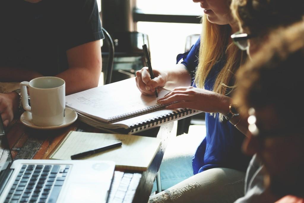 Henkilö kirjoittaa muistiinpanoja vihkoon, kuvassa pöydällä myös kahvikuppi ja tietokone, pöydän ympärillä näkyy muitakin henkilöitä.