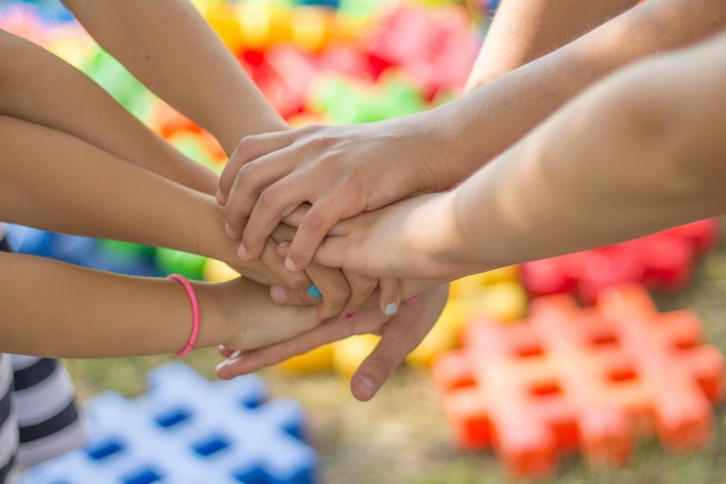 Kuvassa usean henkilön kädet toisiinsa liittyneinä, taustalla värikkäitä elementtejä.