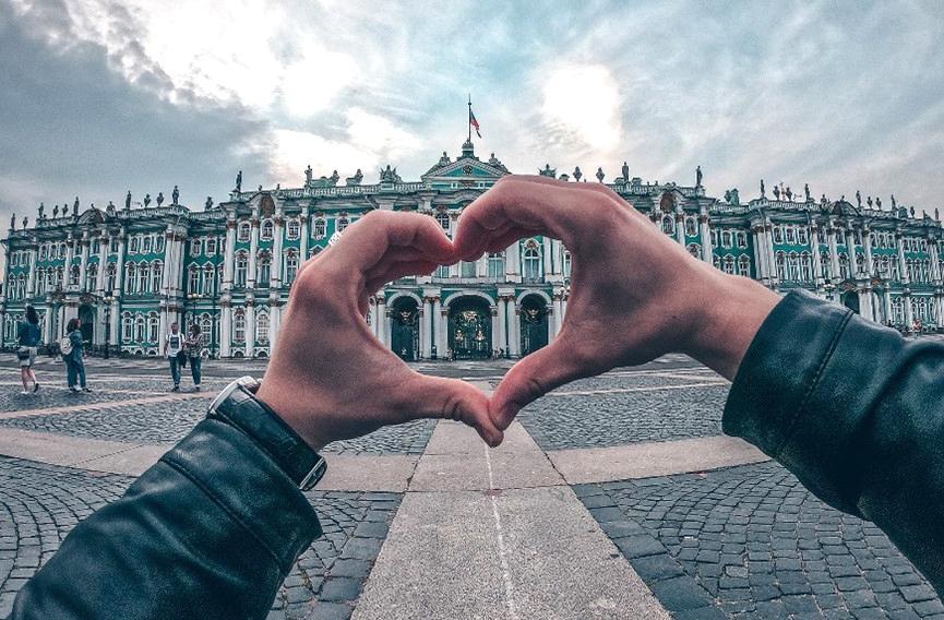 Vanhoja, koristeellisia rakennuksia, kuvan etualalla henkilö muodostaa sormillaan sydänkuvion, jonka läpi näkyy osa rakennuksista.