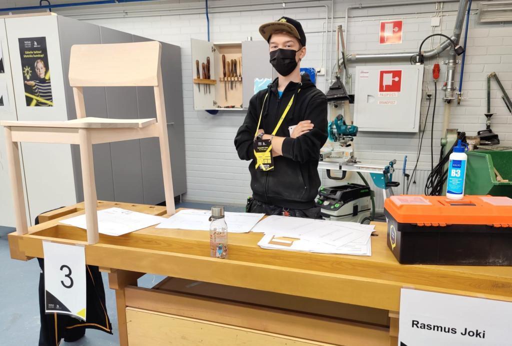 Henkilö työpöydän takana maski kasvoillaan, pöydällä puinen tuoli, työpiirrustuksia sekä työkalupakki, pöydän reunassa kyltti, jossa teksti Rasmus Joki.