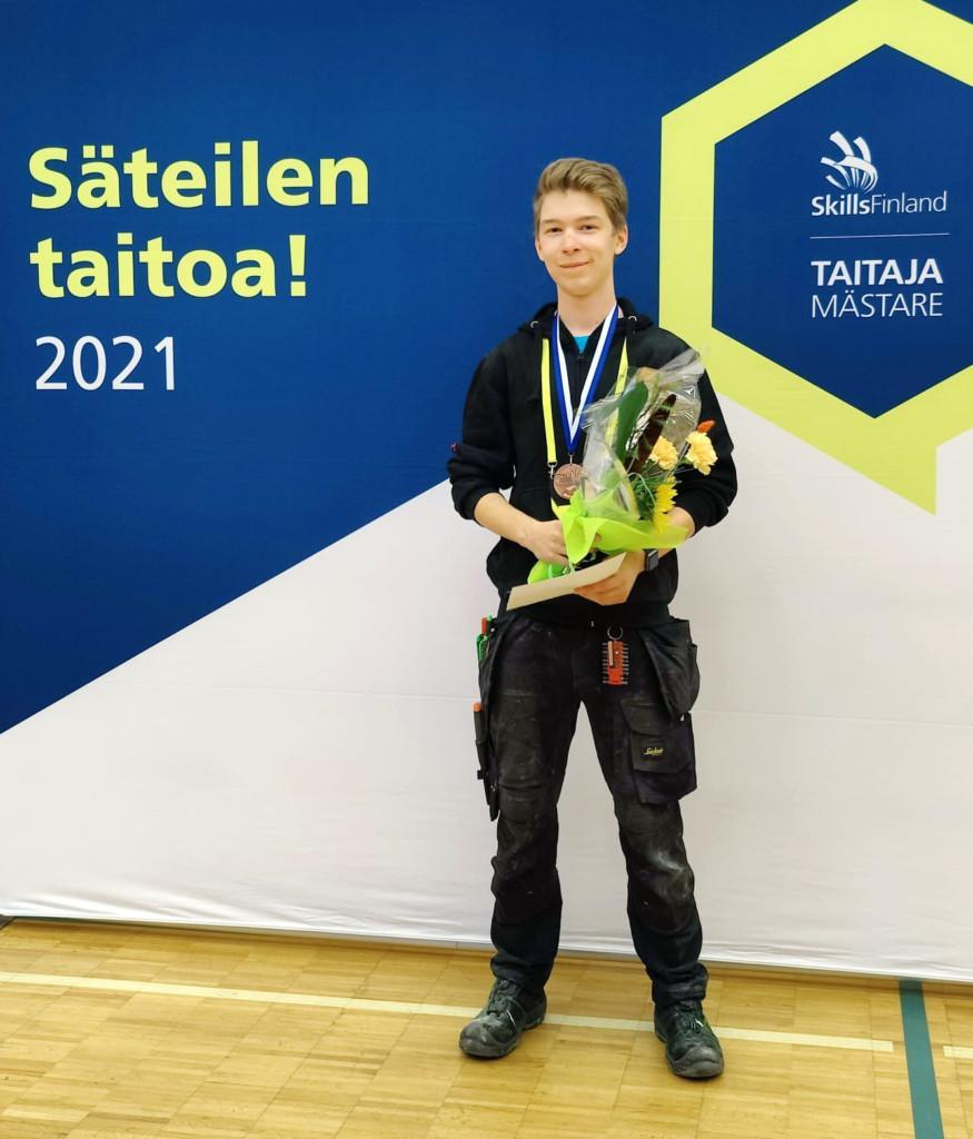 Henkilö, Rasmus Joki seisoo kukkakimppu kädessään ja mitali kaulassaan, taustalla olevalla seinällä tekstit Säteilen taitoa 2021 ja Taitaja Mästare.