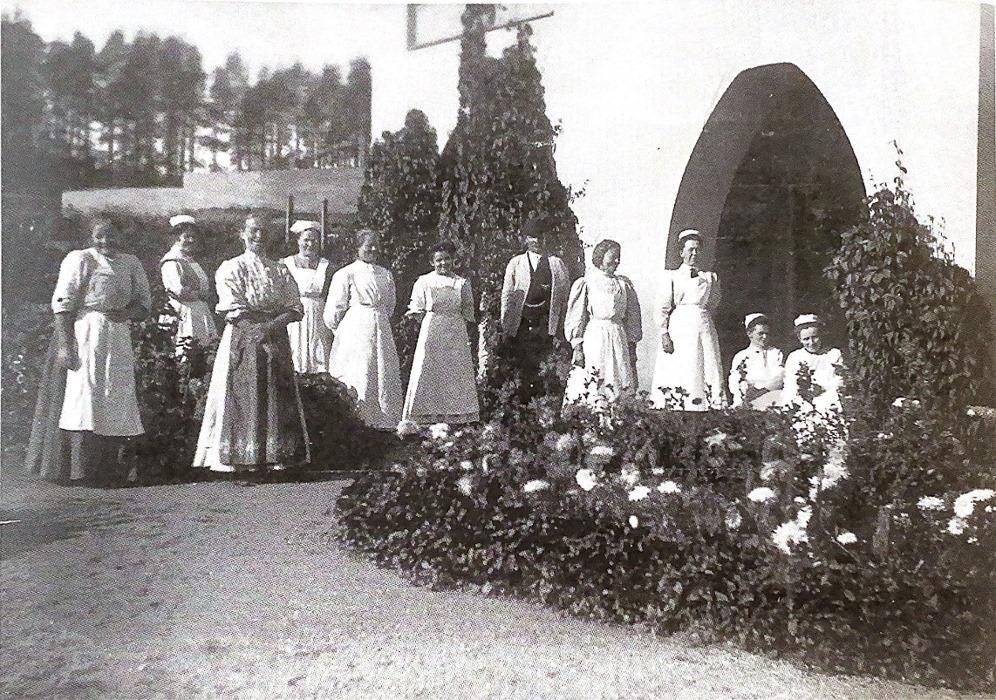 Mustavalkoinen vanha valokuva, jossa pitkiin mekkoihin pukeutuneita naisia ja yksi mies talon edessä, etualalla kukkivia pensaita.