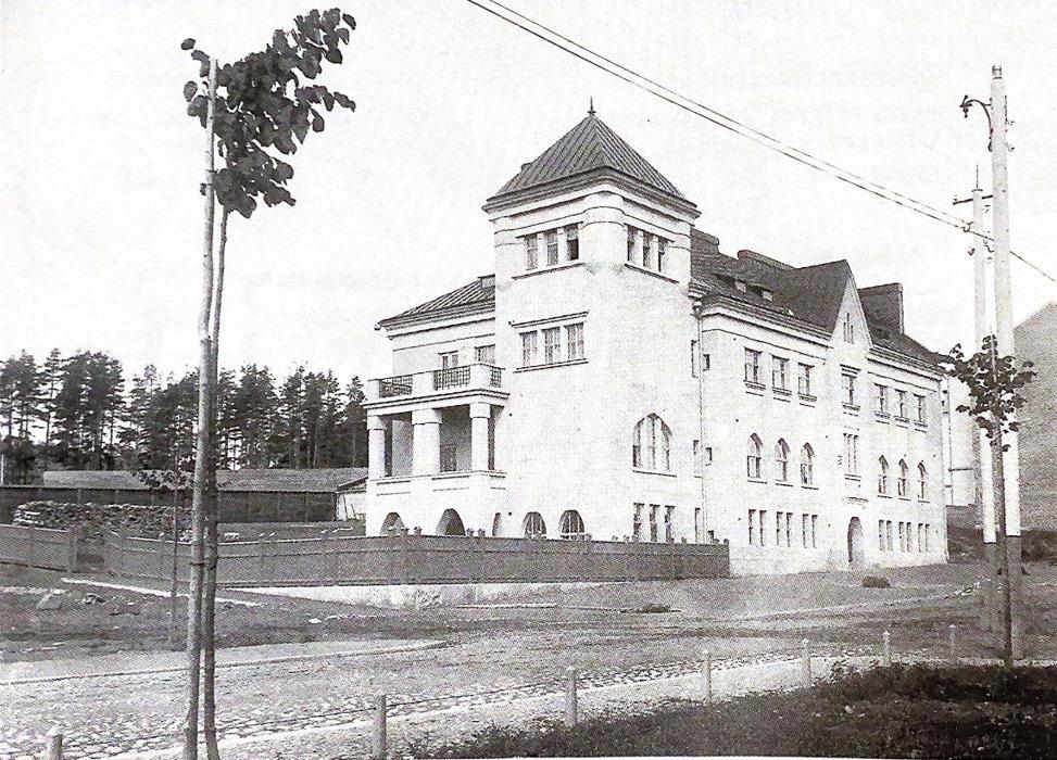 Mustavalkoinen vanha valokuva rakennuksesta, jonka kulmassa tornimainen osa.