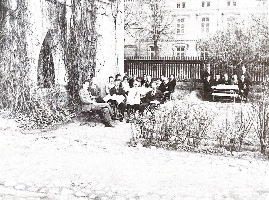 Mustavalkoinen vanha valokuva, jossa joukko miehiä istuu rakennuksen edessä penkeillä, henkilöt katsovat kameraan ja hymyilevät.