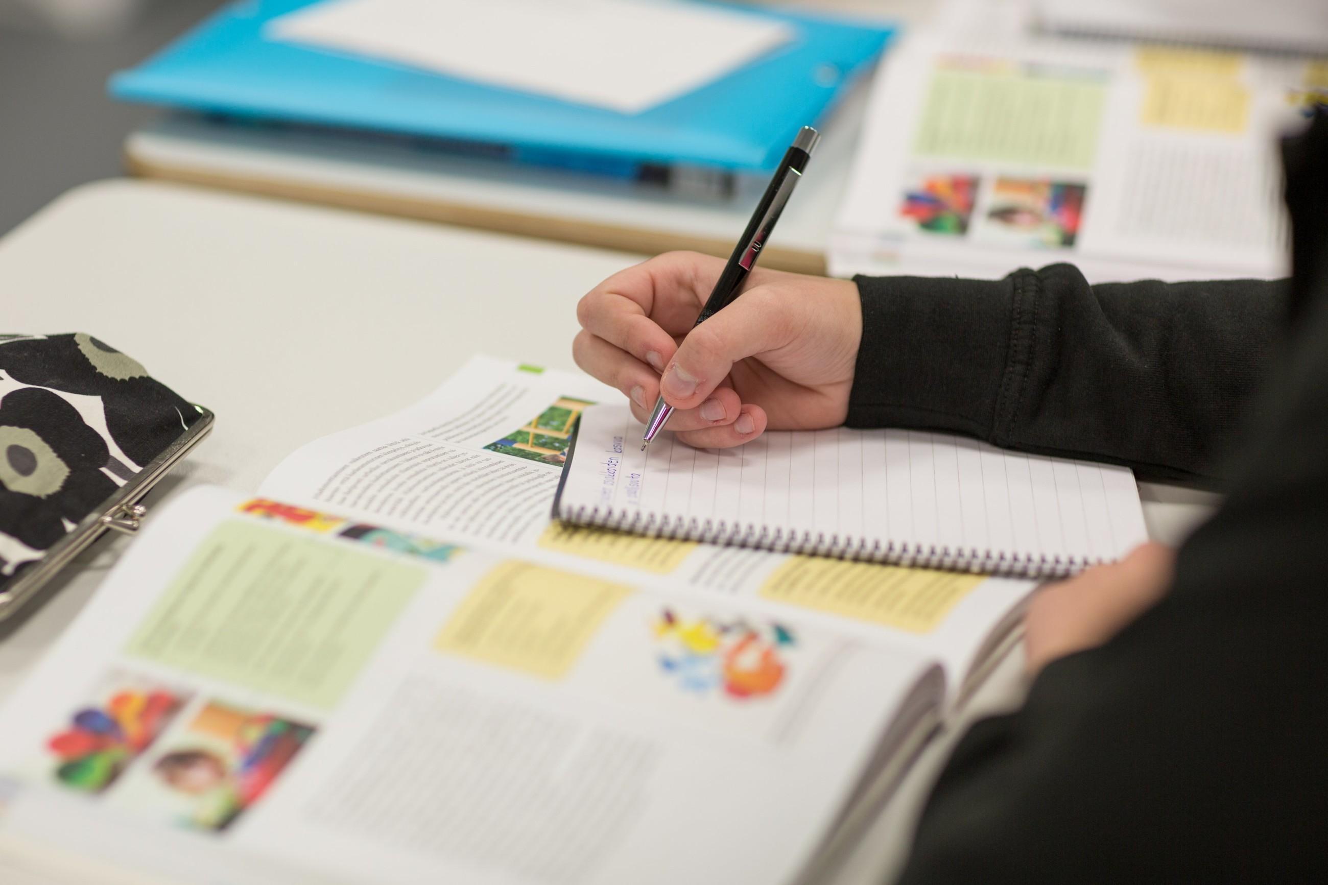 Lähikuva tilanteesta, jossa henkilö kirjoittaa muistiinpanoja vihkoon, pöydällä näkyy myös oppikirjoja ja kukallinen kynäpenaali.