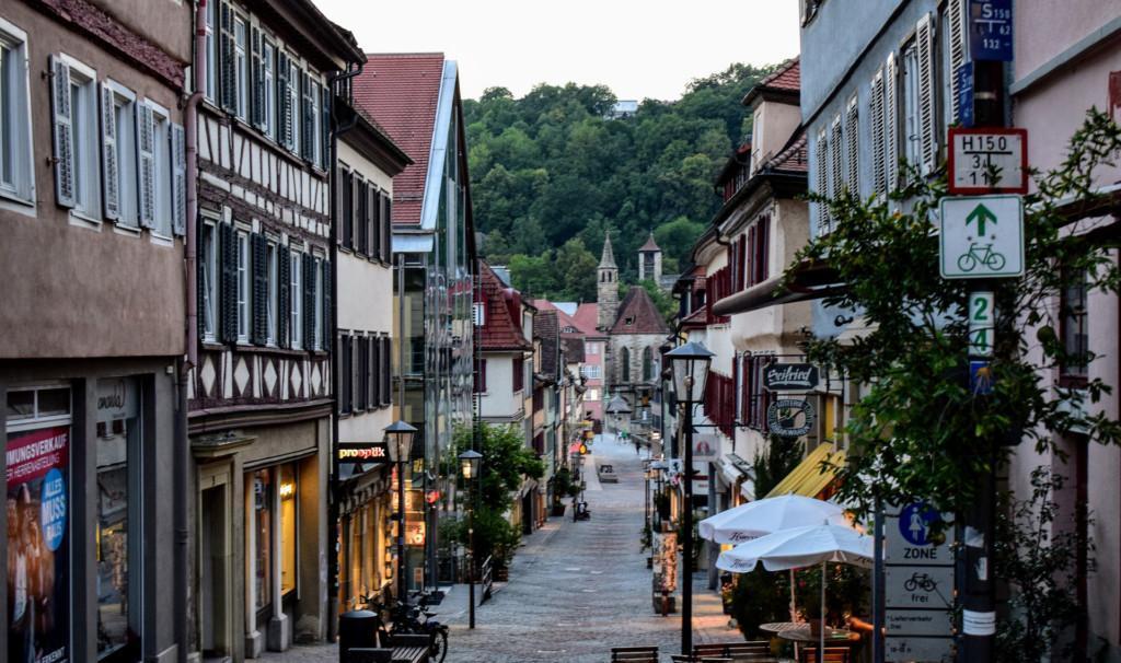 Katunäkymä, kadun varrella liikkeitä ja kahviloita, taustalla kadun päässä näkyy kirkontorni ja metsää.