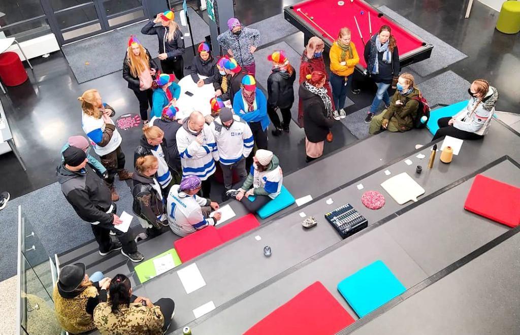 Henkilöitä aulatilassa pukeutuneina mm. pelipaitoihin ja propelilippiksiin, kuvassa näkyy myös biljardipöytä, kuva otettu ylhäältä päin.